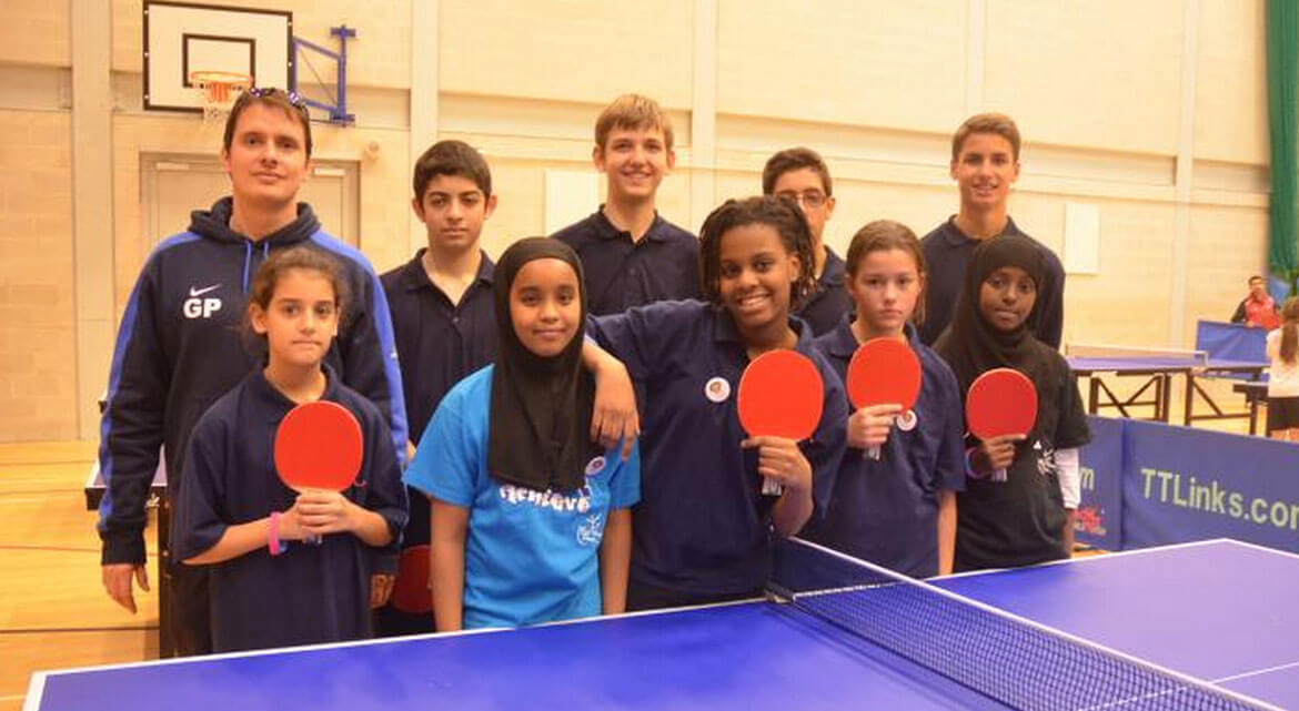Gabor Papp, one of the owners of clueQuest with a team of students as a table tennis teacher